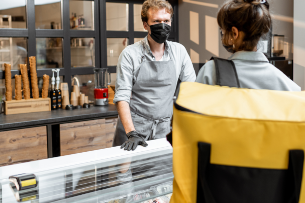Cover image: 5 ways to rethink your swag strategy -Deli clerk wearing a mask helping a customer