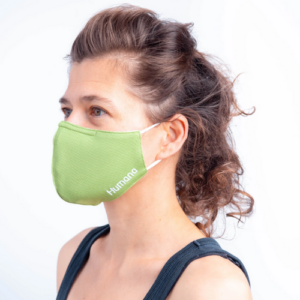 Woman wearing a brite green face mask that says Humana