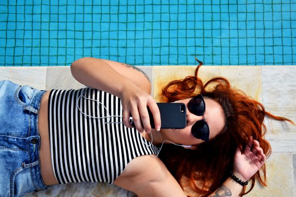 woman laying on the ground taking a selfie by the pool