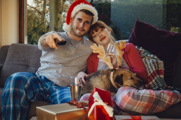 young couple wearing pajamas sitting on the couch with pet dog wearing reindeer antlers. man holding a remote wearing a santa hat