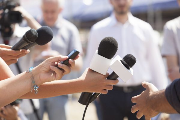 reporters with microphones out