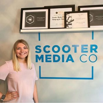 Picture of Hannah Jones posing with the Scooter Media sign