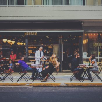 People outside a cafe drinking and eating