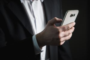 Man in business suit holding cell phone