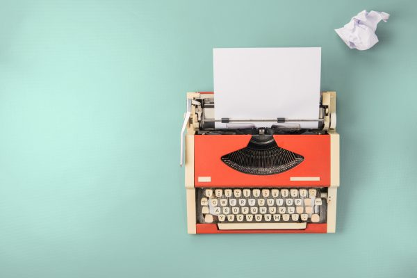 red typewriter on teal background