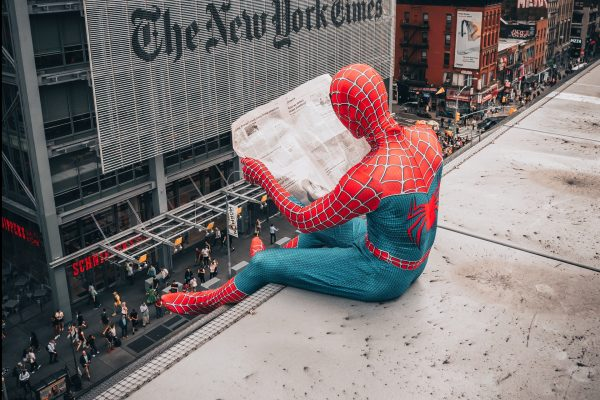 Spiderman sitting on a ledge reading a newspaper by the New York Times building