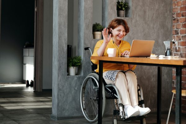 Women in orange top sitting in black wheelchair at a table with a laptop