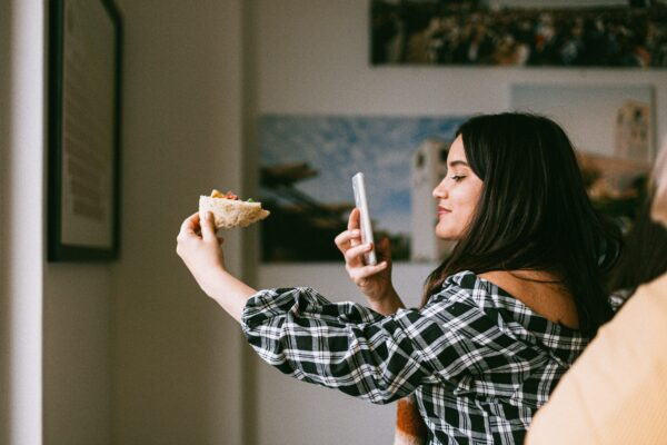 A woman uses her smartphone to take a picture of her upcoming meal