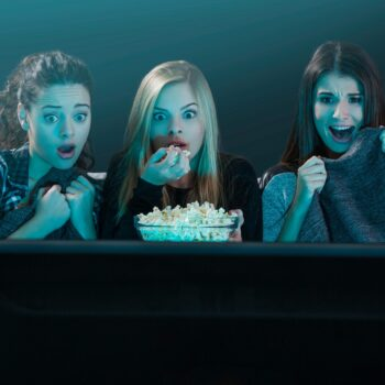 A trio of horror movie fans are glued to the screen.