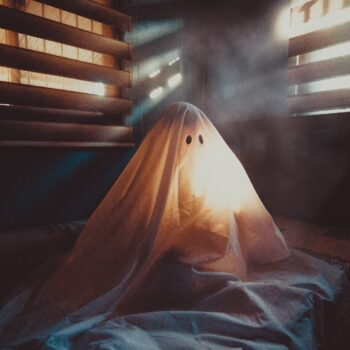 "Someone sitting under a ""ghost"" costume sheet with light coming through the blinds"