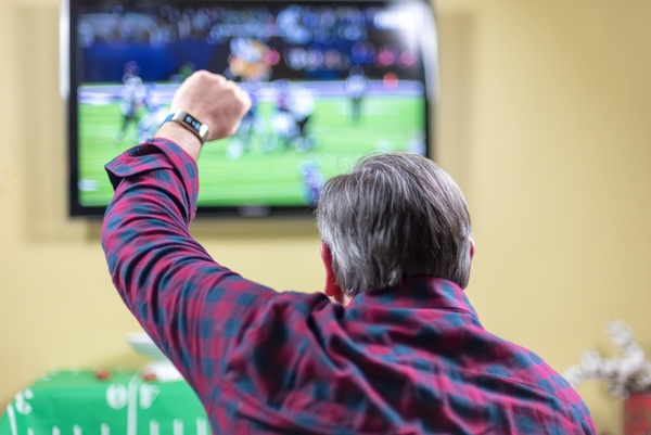 Man sitting on couch cheering at game on TV