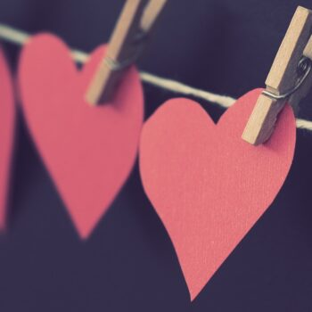 construction paper hearts attached to a string by clothespins