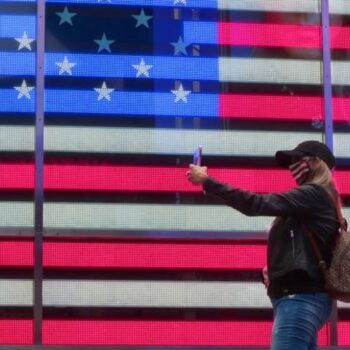 Woman taking selfie in front of the American flag