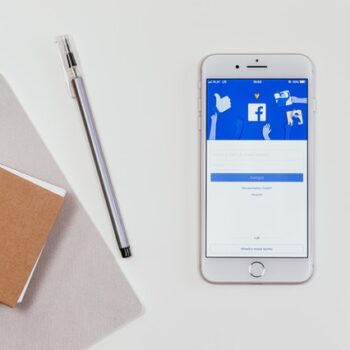 Phone displaying Facebook next to notebooks and creative materials