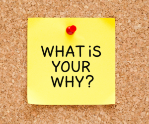 """A yellow post-it note with the questions """"What is your why?"""" on a cork board"""