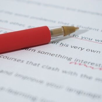 A paper marked in red pen with proofreading marks