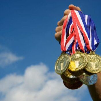 Outstretched hand holding a group of gold medals