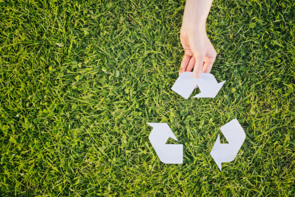 Hand making complete a recycling symbol over green grass