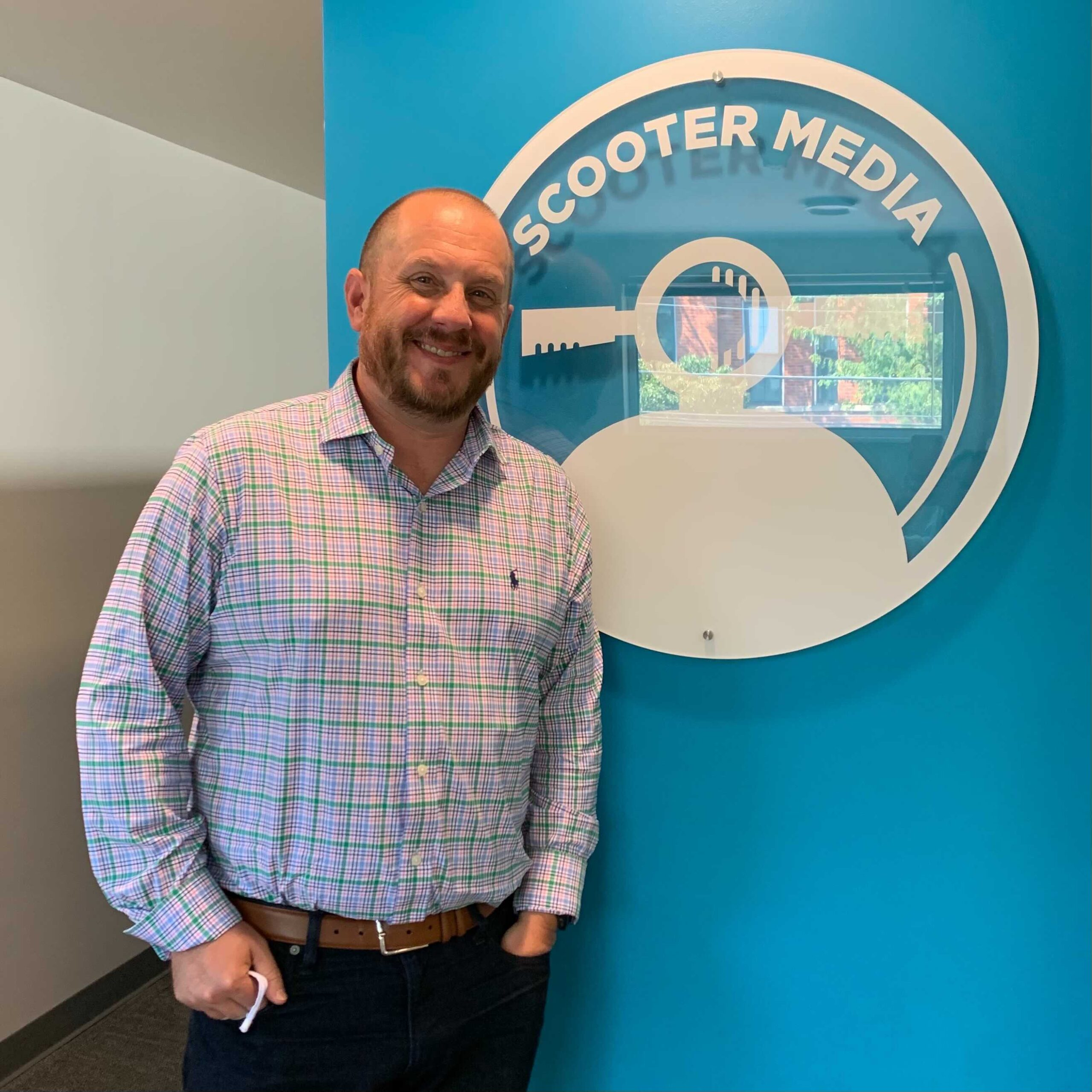 Photo of Brian Mains posing with the Scooter Media logo
